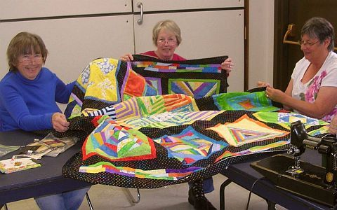 three quilters with a manycolored quilt.