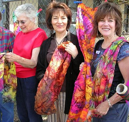 Three women hold up shibori fabric by a chainlink fence