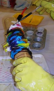 Hands in yellow gloves put dye on silk wrapped round a tube.