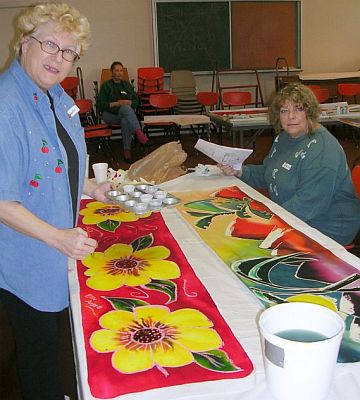 Two women painting silk scarves: yellow flowers on red